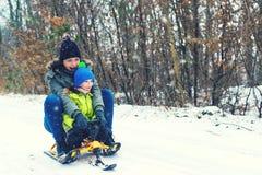 Lycklig moder och hennes son som tycker om släderitt Lycklig familj med släden i vintern som har gyckel tillsammans Sledding för  royaltyfri fotografi