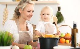 Lycklig moder och liten dotter som lagar mat i kök Spendera all tid tillsammans, roligt begrepp för familj royaltyfria foton