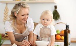 Lycklig moder och liten dotter som lagar mat i kök Spendera all tid tillsammans, roligt begrepp för familj arkivbilder