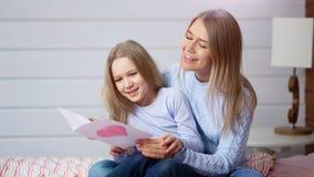 Lycklig moder och liten gullig dotterinnehavvykort med röd hjärta som firar lyckliga moders dag arkivfilmer