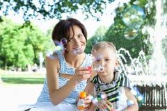 Lycklig moder och liten son med såpbubblor utomhus Fotografering för Bildbyråer
