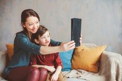 lycklig moder- och litet barnson som hemma använder minnestavlan arkivbilder