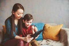 lycklig moder- och litet barnson som hemma använder minnestavlan arkivfoton
