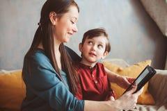 lycklig moder- och litet barnson som hemma använder minnestavlan royaltyfri fotografi