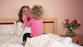 Lycklig moder och litet dottersammanträde på säng och att spela arkivfilmer