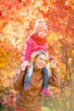 Lycklig moder och och le ungen tillsammans som är utomhus- i höst arkivfoto