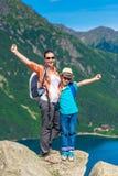 Lycklig moder och son med ryggsäckar som är höga i bergen Fotografering för Bildbyråer