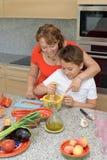 Lycklig moder och son som förbereder lunch med en mortel arkivbilder
