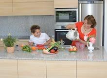 Lycklig moder och son som förbereder lunch Sonen ser hans moder arkivfoton
