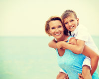 Lycklig moder och son som har gyckel på stranden Royaltyfria Foton