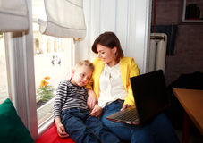 Lycklig moder och son som hemma ser bärbara datorn Royaltyfria Bilder