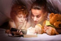 Lycklig moder och son som läser en bok under filten arkivbild