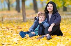 Lycklig moder och son som sitter i gula nedgångsidor royaltyfria foton