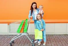 Lycklig moder och två barn med spårvagnvagnen och shoppingpåsen Royaltyfri Foto