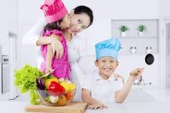 Lycklig moder och ungar med grönsaker royaltyfria foton