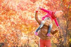 Lycklig moder och unge som har utomhus- gyckel tillsammans i höst Royaltyfri Fotografi