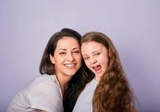 Lycklig moder och upphetsad joying ungeflicka som kramar med emotionella le framsidor på purpurfärgad bakgrund med tomt kopiering arkivfoton