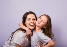Lycklig moder och upphetsad joying ungeflicka som kramar med emotionella le framsidor p? purpurf?rgad bakgrund med tomt kopiering royaltyfri bild