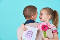 lycklig moder s för dag Gullig liten flicka som ger den mammahälsningkortet, gåva och buketten av rosa gerberatusenskönor Fostra  Royaltyfri Bild