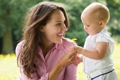 Lycklig moder som ger blomman för att behandla som ett barn i parkera Royaltyfria Foton