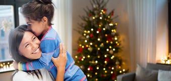Lycklig moder som kramar hennes dotter på jul royaltyfria bilder