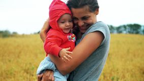Lycklig moder som kramar le barnet i fältet med vete stock video