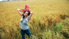 Lycklig moder som kramar le barnet i fältet med vete lager videofilmer