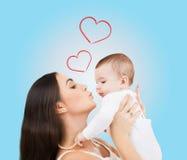 Lycklig moder som kysser hennes barn Royaltyfria Bilder