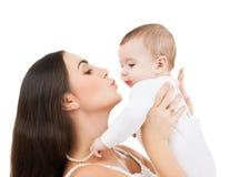 Lycklig moder som kysser hennes barn Fotografering för Bildbyråer