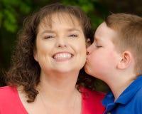 Lycklig moder som ler på kyssen från son Arkivfoto