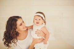 Lycklig moder som lite rymmer flickan royaltyfri foto