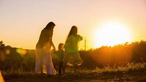 Lycklig moder som spelar med den lilla sonen på solnedgången lager videofilmer