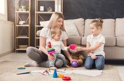 Lycklig moder som spelar med hennes döttrar fotografering för bildbyråer