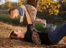 Lycklig moder som spelar med hennes son som är utomhus- i höst arkivfoton