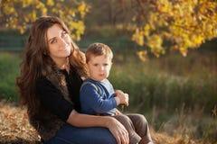 Lycklig moder som spelar med hennes son som är utomhus- i höst royaltyfri fotografi