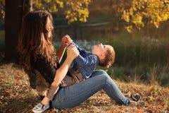 Lycklig moder som spelar med hennes son som är utomhus- i höst Royaltyfria Bilder