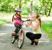Lycklig moder som talar med hennes dotter som ler, som undervisar till att cykla Royaltyfria Bilder