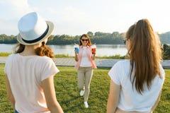 Lycklig moder som vilar på naturen med hennes tonårs- döttrar 14 och 16 gamla år Kommunikation av föräldrar och tonåringar, kvinn royaltyfri foto