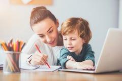 Lycklig moder som visar hennes son hur man skriver royaltyfri fotografi