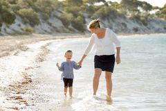 Lycklig moderinnehavhand av den söta blonda lilla dottern som tillsammans går på sand på strandhavskusten fotografering för bildbyråer