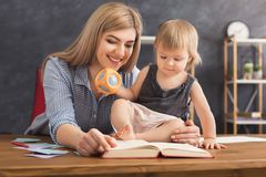 Lycklig moderläsning med hennes dotter arkivbild