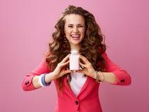 Lycklig modern kvinna på organisk yoghurt för rosa visninglantgård arkivfoton