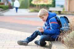 Lycklig modern pojke med mobiltelefonen Royaltyfria Bilder