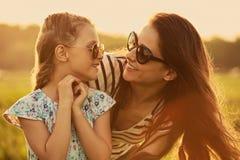 Lycklig modeungeflicka som omfamnar hennes moder i moderiktig solglas?gon och ser sig med f?r?lskelse p? naturbakgrund closeup royaltyfri foto