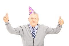Lycklig mogen gentleman med partihatten som ger upp tummar Arkivfoton