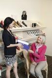 Lycklig mogen kund som tar skodonasken från mitt- affärsbiträde för vuxen kvinnlig i skolager Fotografering för Bildbyråer
