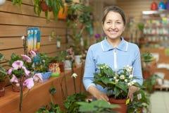 Lycklig mogen kvinna på blommalagret Arkivbilder