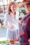 Lycklig mogen kvinna som köper nya organiska grönsaker i en lokal marknadsplats arkivbild