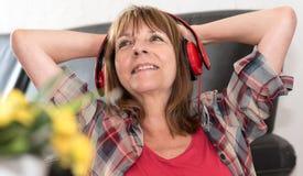 Lycklig mogen kvinna som lyssnar till musik royaltyfria bilder