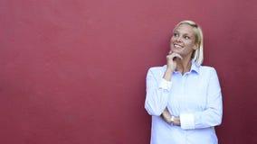 Lycklig mogen kvinna som tänker på röd bakgrund arkivfilmer